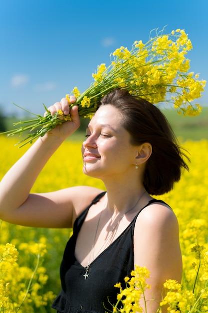 Молодая девушка мечтает о желтом поле рапса на голубом небе летом Premium Фотографии