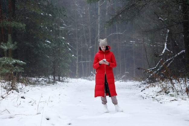 冬の森には、長い赤い羽毛のコートを着た少女が立っています。 Premium写真