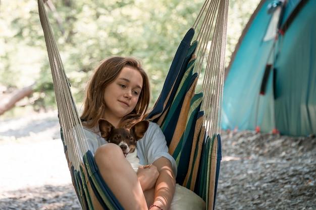 犬と一緒にハンモックでリラックスした少女。森で休んでいる女の子、ハンモックでキャンプ。森の中の健康的なライフスタイル。 Premium写真