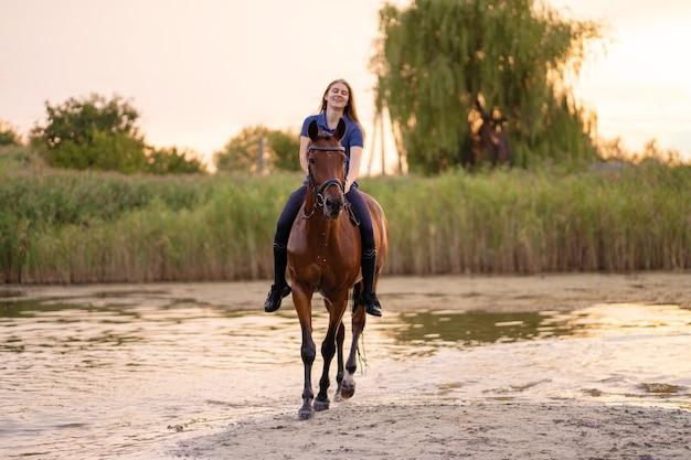 Молодая девушка на лошади на мелководном озере. лошадь бежит по воде на закате Premium Фотографии