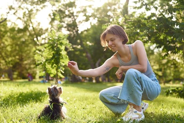 Молодая девушка бегает и играет в зеленом парке со своим йоркширским терьером. Premium Фотографии