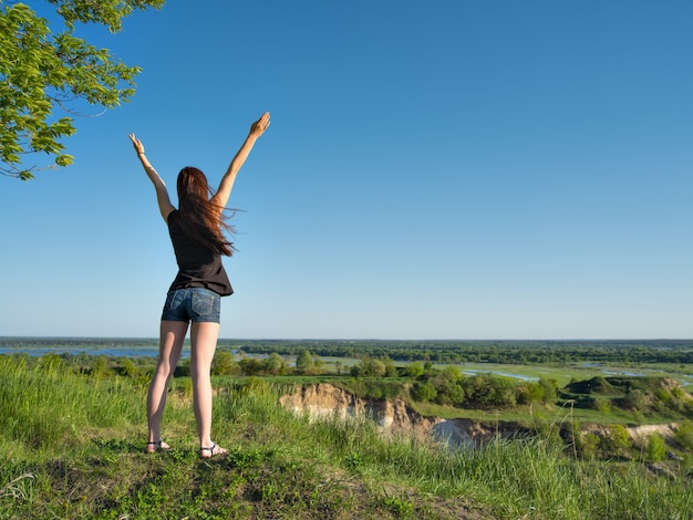 腕を上げて立っている少女。眺めを眺めるリラックスした若い女性。風景を楽しむ崖のそばに立っている平和な少女。 -屋外。フルレングスのポートレート 無料写真