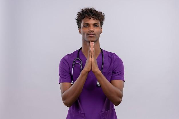 Молодой симпатичный темнокожий мужчина-врач с кудрявыми волосами в фиолетовой форме со стетоскопом, держащим руку вместе Бесплатные Фотографии