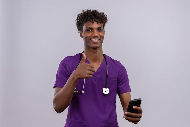 Молодой симпатичный темнокожий мужчина-врач с кудрявыми волосами в фиолетовой форме со стетоскопом держит смартфон и показывает жест «ок» Бесплатные Фотографии