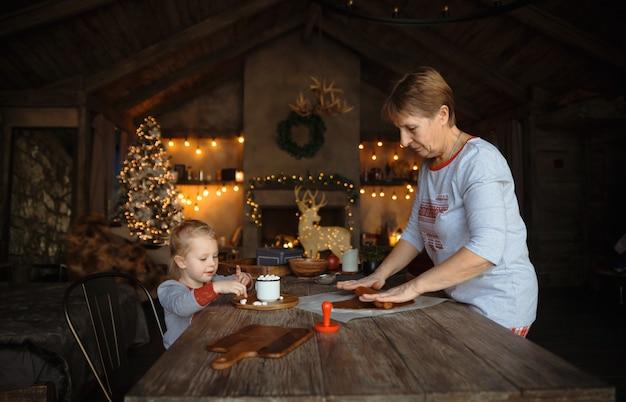 Молодая бабушка и ее внучка вместе готовят печенье. Premium Фотографии