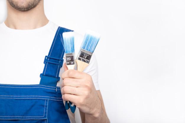 Молодой парень в синем комбинезоне держит строительную кисть в руке. Premium Фотографии