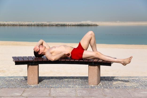 Молодой парень в красных плавках загорает, лежа на скамейке у пляжа. Premium Фотографии
