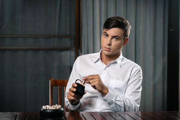 Молодой парень позирует сидя за столом, на котором стоит пепельница Premium Фотографии