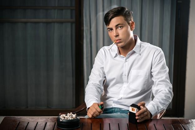 Молодой парень позирует сидя за столом, на котором стоит пепельница, полная сигарет Premium Фотографии