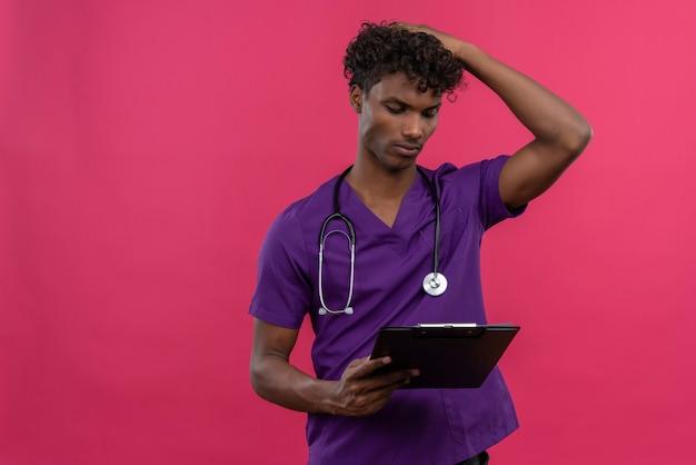 クリップボードを見て聴診器で紫の制服を着た巻き毛の若いハンサムな浅黒い肌の医者 無料写真