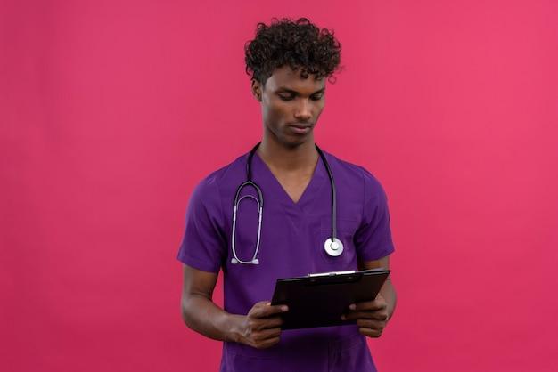 クリップボードを見て聴診器で紫の制服を着ている巻き毛の若いハンサムな浅黒い医者 無料写真