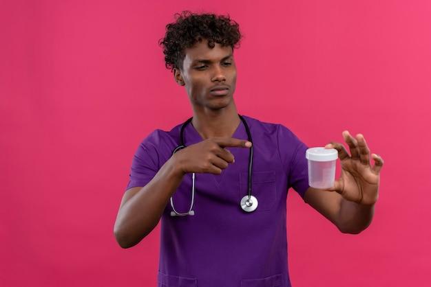 医療用プラスチック標本瓶に人差し指で聴診器を向けて紫の制服を着た巻き毛の若いハンサムな浅黒い医者 無料写真