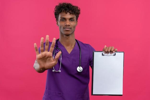 紙の空白のシートでクリップボードを示す聴診器で紫の制服を着た巻き毛の若いハンサムな浅黒い医者 無料写真
