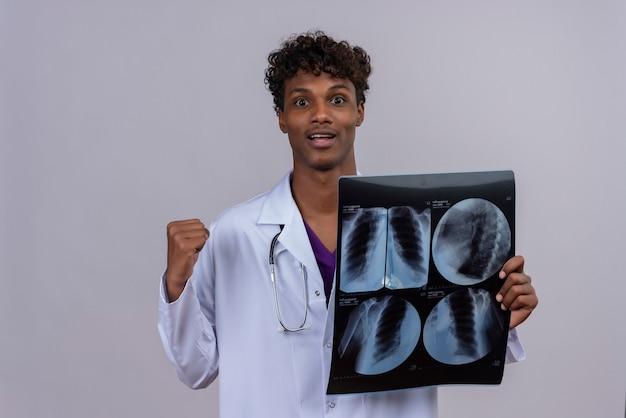 X線レポートを表示しながら聴診器で幸せを感じて白いコートを着た巻き毛の若いハンサムな浅黒い男性医師 無料写真