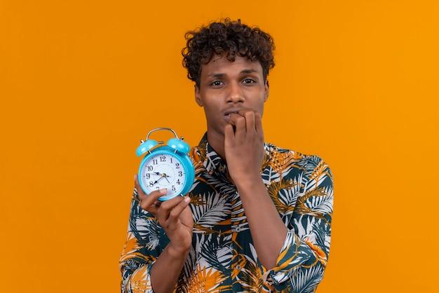 あごに手で青い目覚まし時計を保持している葉のプリントシャツの葉の巻き毛を持つ若いハンサムな浅黒い肌の男 無料写真