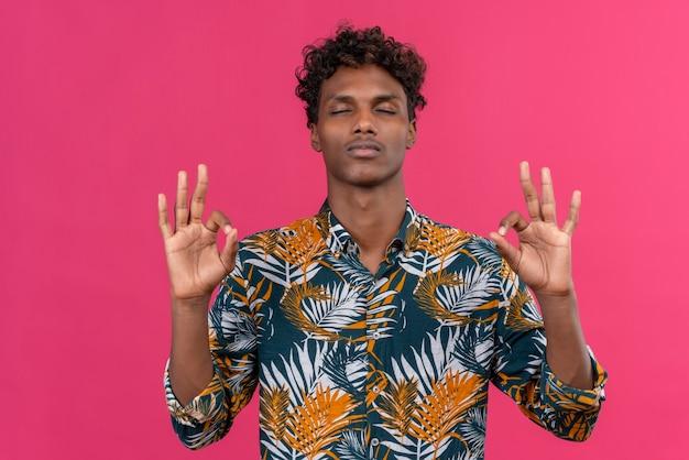葉に巻き毛のある若いハンサムな浅黒い肌の男がプリントされたシャツをokサインで手をつないでリラクゼーションと瞑想で目を閉じて 無料写真