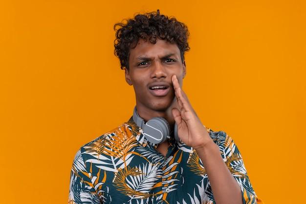 Молодой красивый темнокожий мужчина с вьющимися волосами в рубашке с принтом листьев и агрессивным лицом зовет кого-то, держащего руку на лице Бесплатные Фотографии