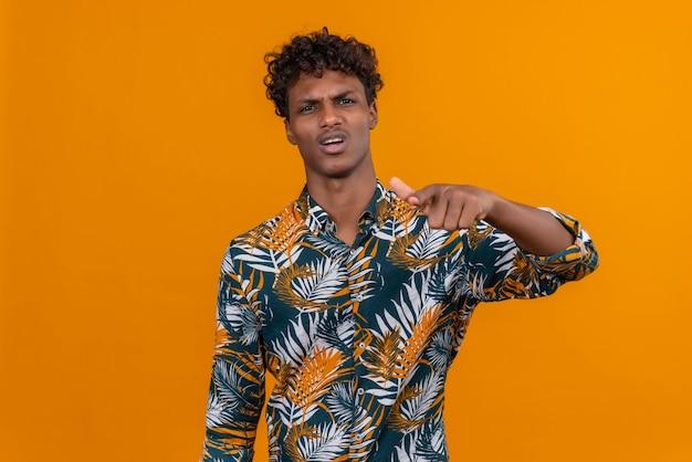 Молодой красивый темнокожий мужчина с кудрявыми волосами в рубашке с рисунком из листьев с сердитым и агрессивным выражением лица указывает в камеру указательным пальцем Бесплатные Фотографии