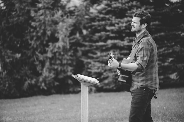 ギターを持ってキリスト教の賛美歌の本から歌を演奏している公園の若い男性 無料写真