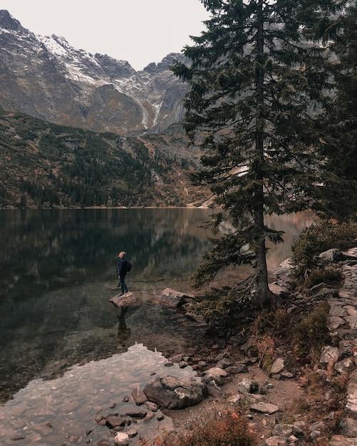 高山に囲まれた澄んだ紺碧の緑の湖の真ん中にあるビッグストーンの上に、フードをかぶった男が立っている若い男 Premium写真