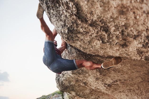若い男の登山家が岩を登ります。 無料写真