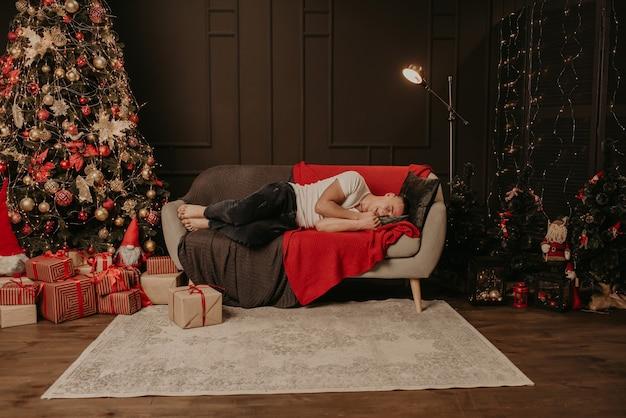 Молодой человек заснул на диване возле елки. украшенный дом на новый год Premium Фотографии