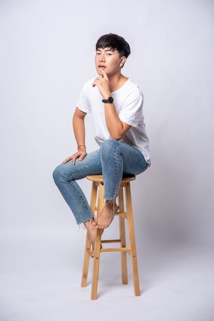 白いtシャツを着た若い男性が高い椅子に座っています。 無料写真