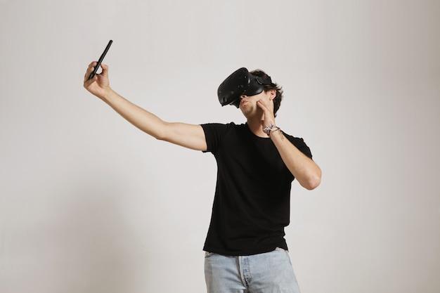 黒のtシャツとvrヘッドセットを身に着けているジーンズの若い男は、白で隔離された彼のスマートフォンで自分撮りをしながらアヒルの顔を作ります 無料写真