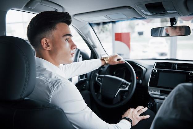 Молодой человек садится в недавно купленную машину за рулем, удачная покупка. Бесплатные Фотографии
