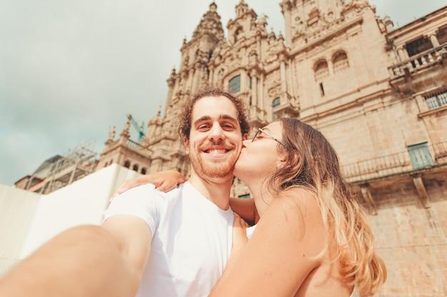 Молодой человек делает селфи и улыбается, пока его девушка целует его Premium Фотографии