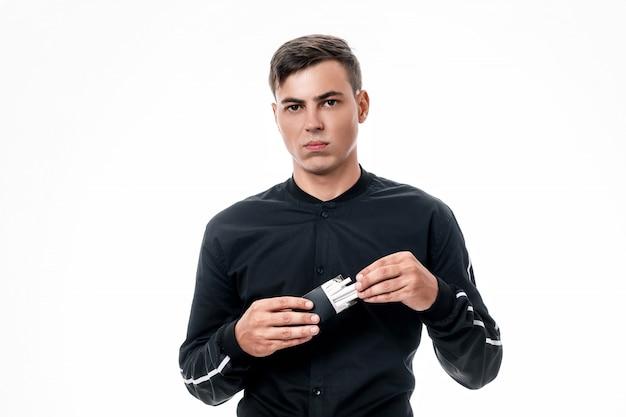 真面目な顔をした若い男は、黒いパックからタバコを取り出します。悪い習慣。喫煙をやめる。孤立した背景。 Premium写真