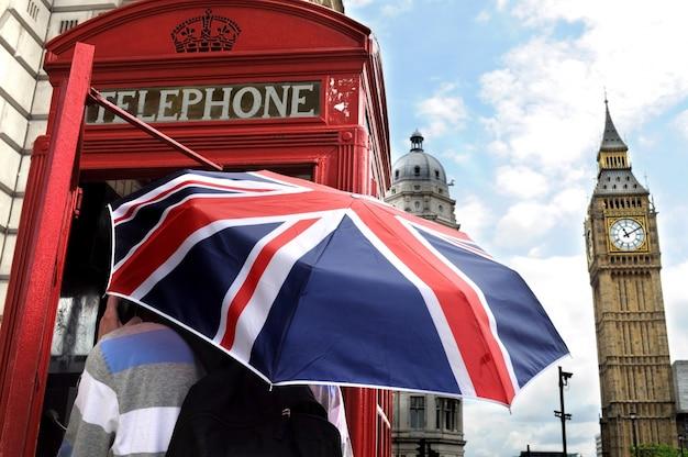 Турист с британским зонтиком в телефонной будке в лондоне Бесплатные Фотографии