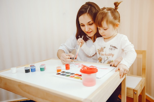 A young mother, along with her little daughter paints on paper Free Photo