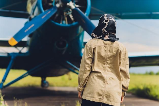 Молодая мусульманка в платке стоит на фоне старого самолета. Premium Фотографии