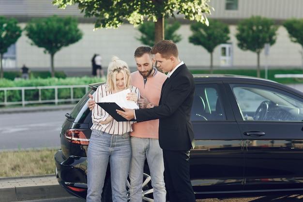 若いセールスマンが新しい車を顧客に見せます。幸せなカップル、男性と女性が新しい車を購入します。若い人たちは車を買うために書類に署名します。 Premium写真