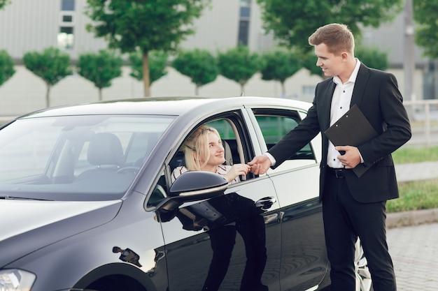 若いセールスマンが新しい車を顧客に見せます。幸せな女性は新しい車を購入します。若い女性がハンドルを握っていて、売り手は彼女に鍵を渡します。 Premium写真