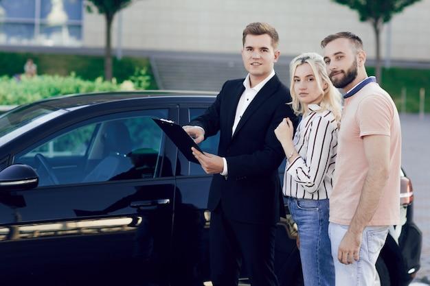 若いセールスマンが新しい車を顧客に見せます。男と女は車を買う。 Premium写真