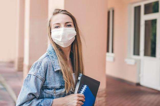 医療用防護マスクを身に着けている若い学生の女の子が大学の建物に入り、ノートブックと練習帳のパックを手に持ってカメラを見る Premium写真