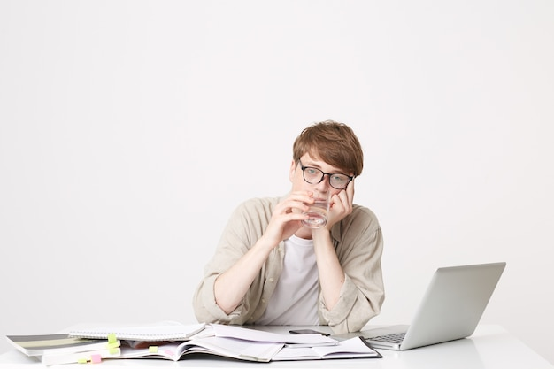 Молодой студент сидит за столом и выглядит очень уставшим Бесплатные Фотографии