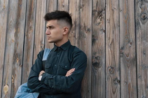 Молодой стильный модельный человек представляя на деревянной предпосылке с backp Premium Фотографии