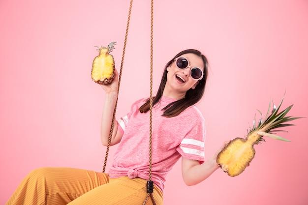 分離されたピンクのブランコに乗って夏の一見でスタイリッシュな女性。 無料写真
