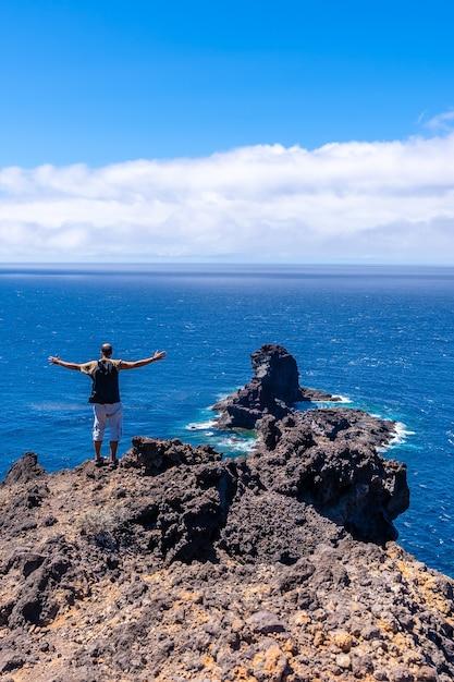 カナリア諸島のラパルマ島の北にあるブハレンの黒い砂のビーチに下りる崖の道にいる若い観光客。スペイン Premium写真