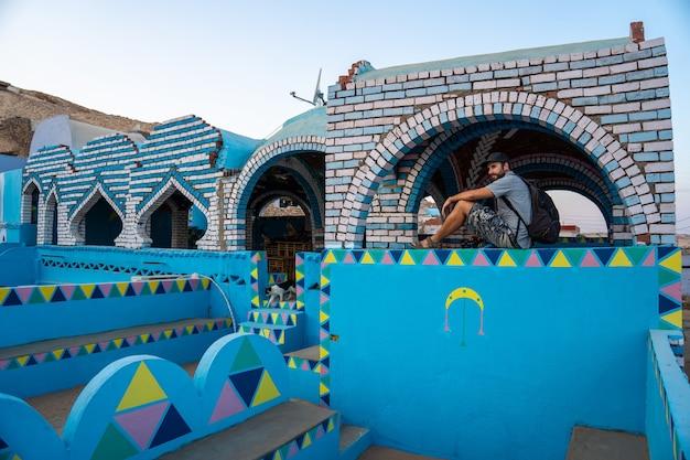 アスワン市近くのヌビアの村にある伝統的な青瓦台の美しいテラスに座っている若い観光客。エジプト Premium写真