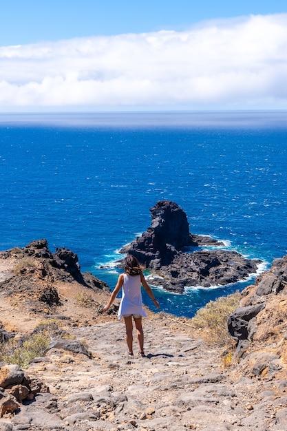 カナリア諸島のラパルマ島の北にあるブハレンの黒い砂のビーチに下りる崖の道を歩く若い観光客。スペイン Premium写真