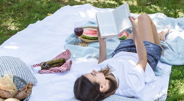 Молодая женщина на пикнике читает книгу Бесплатные Фотографии