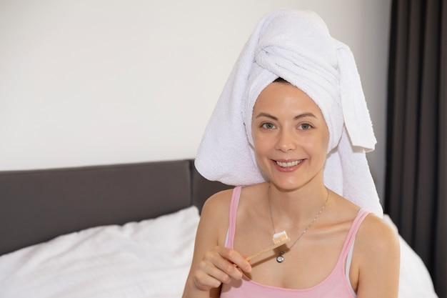 若い女性が天然の竹製歯ブラシで歯を磨く Premium写真