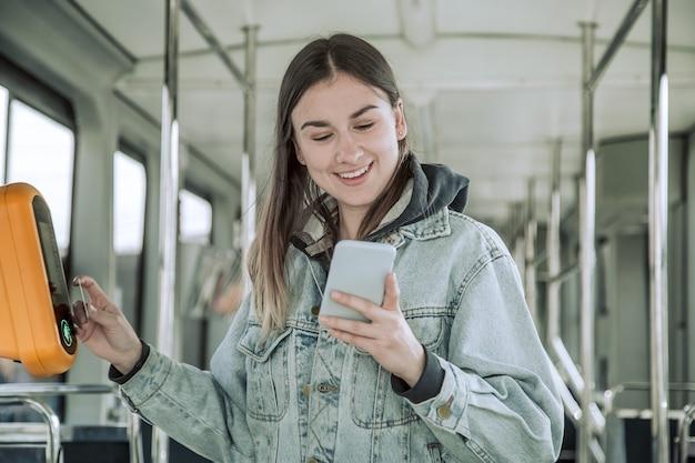 非接触型の若い女性が公共交通機関の料金を支払います。 無料写真
