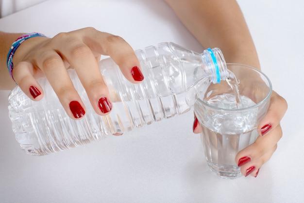 Молодая женщина наполнила стакан водой Premium Фотографии