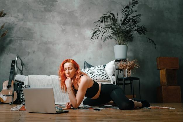 젊은 여성이 집에서 스포츠, 온라인 운동에 들어갑니다. 프리미엄 사진