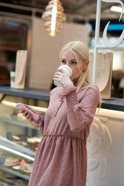 휴대 전화와 그녀의 손에 커피 종이 컵을 들고 쇼핑 센터에있는 카페에서 젊은 여자. 프리미엄 사진